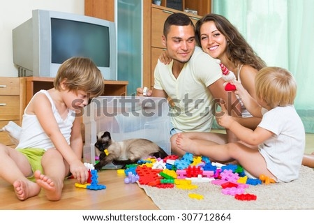 Joyful parents and two little daughters playing with plastic toys in home