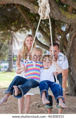 Joyful parents pushing their children on a swing in a park - stock photo