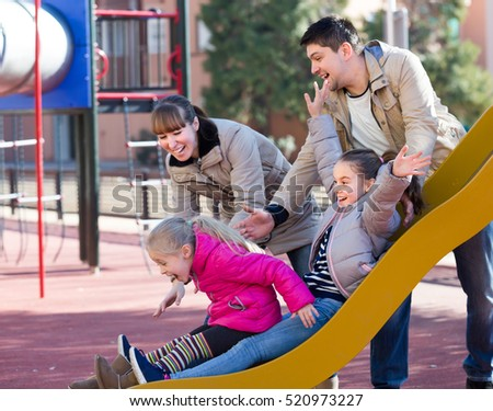 Joyful parents with two excited little daughters having fun at sliding board outdoors . Selective focus
