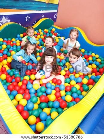 Joyful preschool kids playing in the colorful balls - stock photo