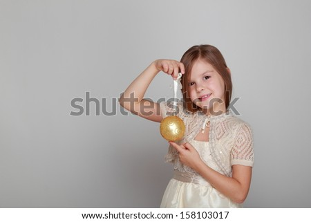 Joyful pretty little girl in a beautiful dress and a cute smile holding a yellow balloon for Christmas tree decorations on a gray background on Holiday
