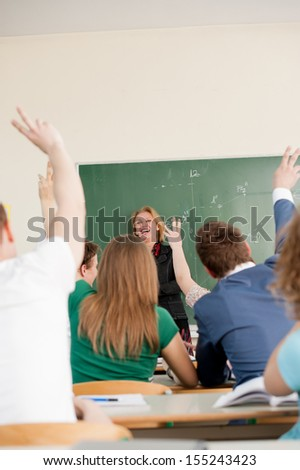 Joyful professor on a chalkboard looking at her students