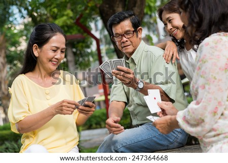Joyful retired people playing cards outdoors - stock photo