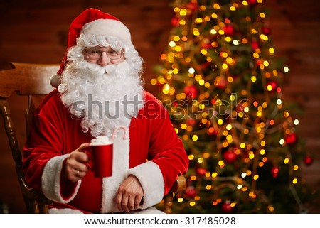 Joyful Santa with cup of latte offering toast for Christmas - stock photo