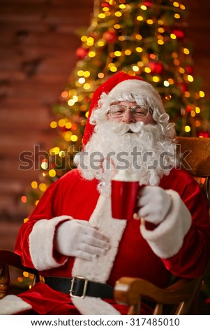Joyful Santa with cup of latte sitting in armchair in front of camera - stock photo