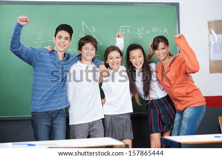 Joyful schoolchildren with hands raised standing together against board in classroom - stock photo