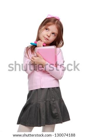 Joyful schoolgirl smiling happily on Education theme/Little schoolgirl holding a pink notebook and pencils - stock photo