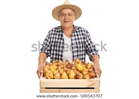 Joyful senior farmer holding a crate full of pears isolated on white background