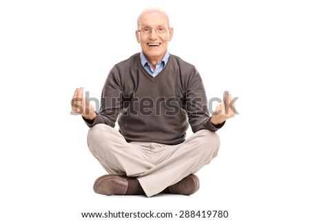 Joyful senior gentleman meditating seated on the floor and looking at the camera isolated on white background
