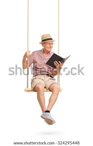 Joyful senior man sitting on a wooden swing and reading a book isolated on white background - stock photo