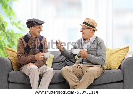 Joyful seniors sitting on a sofa and talking
