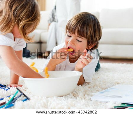 Joyful siblings eating chips and drawing lying on the floor