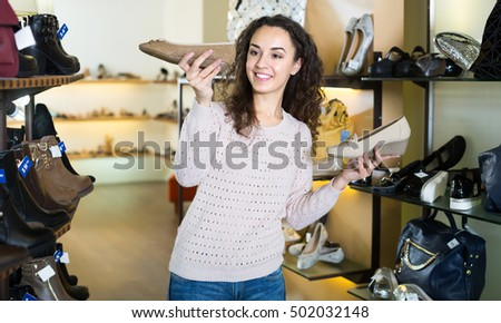 Joyful smiling brunette girl choosing fashion summer shoes in a shoe store