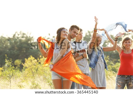 Joyful smiling friends dancing in the forest outdoors - stock photo