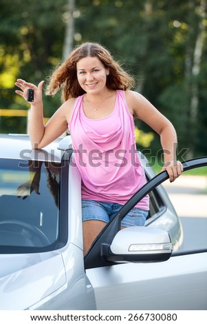 Joyful smiling girl with car keys in hand standing on footboard of vehicle - stock photo