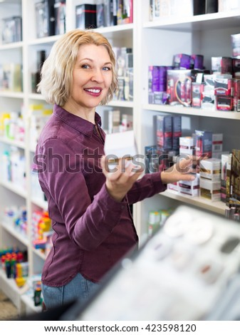 Joyful  smiling mature female seller offering new cosmetics in beauty store