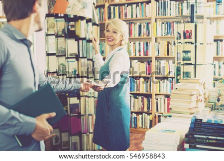 joyful smiling mature woman standing among bookshelves and taking book in book store