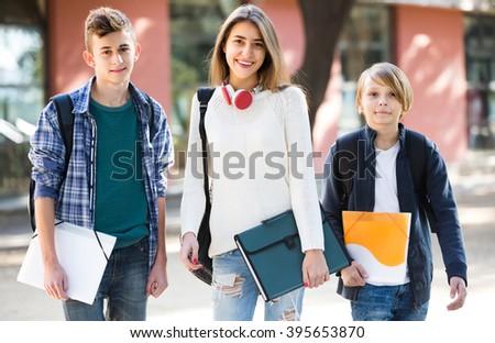 Joyful smiling teenage students going to college through city street - stock photo