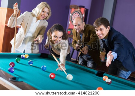 Joyful smiling young and mature couples playing pool in billiard club . Selective focus - stock photo
