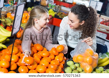 Joyful smiling young woman and little girl choosing fruits at market