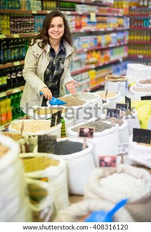 Joyful smiling young woman buying groats in supermarket - stock photo