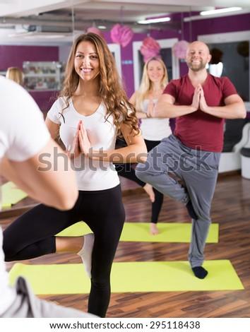 Joyful smilng young adults having yoga class in sport club - stock photo