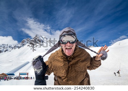 Joyful snowboarder on the background beautiful mountains and blue sky with clouds - stock photo