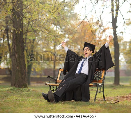 Joyful student celebrating his graduation seated on a bench in a park shot with tilt and shift lens