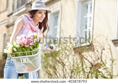 Joyful stylish woman in gray hat  on a bicycle with spring flowers on a background of the city