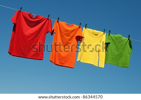 Joyful summer laundry. Colorful t-shirts on a laundry line and blue sky.