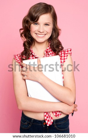 Joyful teenage girl holding spiral notebook. Educational concept - stock photo