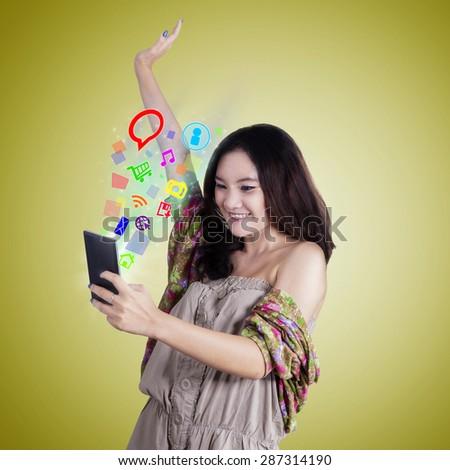 Joyful teenage girl looks happy while using smartphone to access social media - stock photo