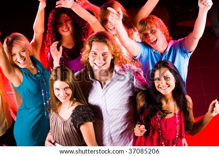 Joyful teens having fun in night club while dancing