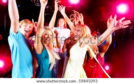 Joyful teens having fun in night club while dancing - stock photo