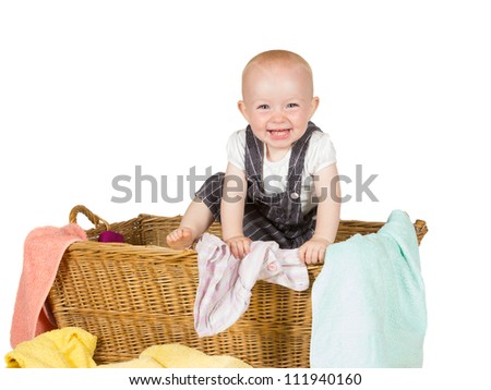Joyful toddler with lovely wide happy smile clambering out of a wicker basket with the laundry scattered around it - stock photo