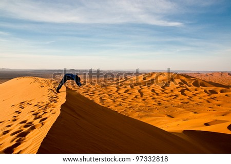 Joyful tourist jumping over sand dune - stock photo