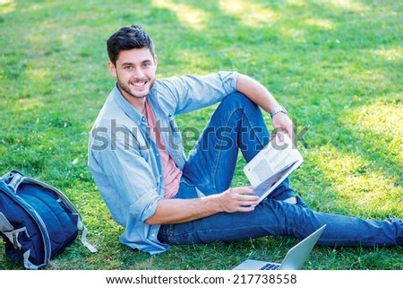 Joyful university life. Cute male student holding a book and looking at the camera while sitting on the grass near the campus of the University at the break. - stock photo