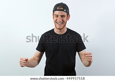 Joyful, Very Happy Smiling Young Adult Male in Dark T-Shirt and Baseball Hat Worn Backwards - stock photo
