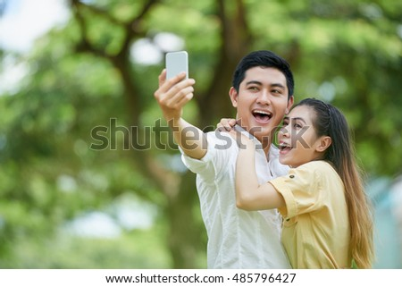 Joyful Vietnamese young couple laughing and taking selfie outdoors