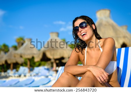 Joyful woman at tropical resort caribbean beach. Summertime vacation tourism and travel concept. Beautiful brunette sunbathing and relaxing at Mayan Riviera, Mexico. - stock photo