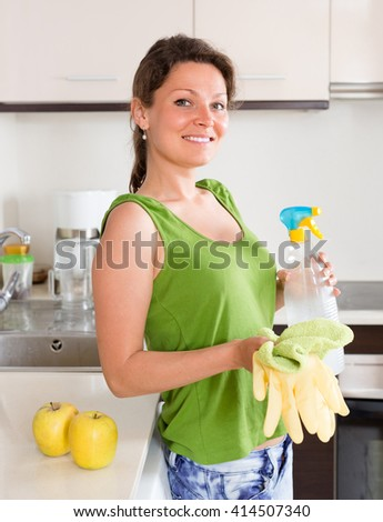 Joyful woman cleaning furniture in kitchen at home
