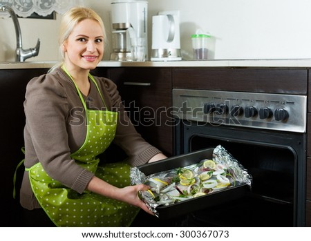 Joyful woman cooking fish  in oven at home kitchen