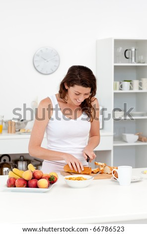 Joyful woman cutting bread for breakfast standing in the kitchen at home - stock photo
