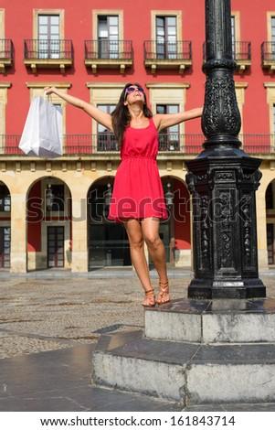 Joyful woman dancing after shopping in Spain.  Successful fashion pretty girl raising white bags. Plaza Mayor of Gijon, Asturias, Spain. - stock photo