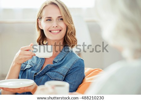 Joyful woman drinking tea with her mother