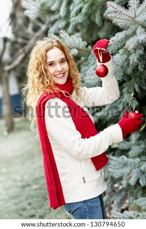 Joyful woman hanging Christmas ornaments on spruce tree outdoors in yard near home - stock photo