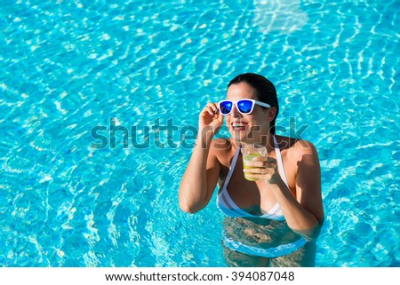 Joyful woman having fun bathing in hotel resort spa pool and drinking cocktail on summer vacation. - stock photo