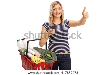 Joyful woman holding a shopping basket and giving a thumb up isolated on white background - stock photo