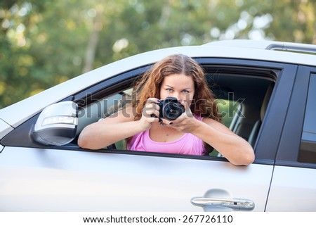 Joyful woman in pink t-shirt with photo-camera in hand taking pictures from car - stock photo