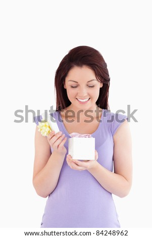 Joyful woman opening a box in a studio